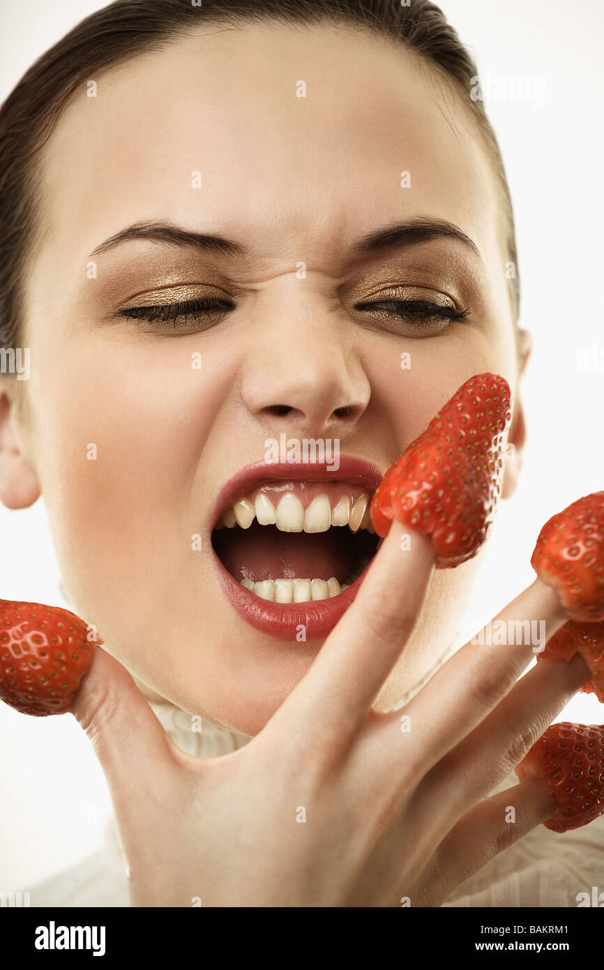 MCtr11k personas mujer morena 20 25 25 30 niña componen frutas fruta fresa fresas dedo mano dedos comer ira Imagen De Stock