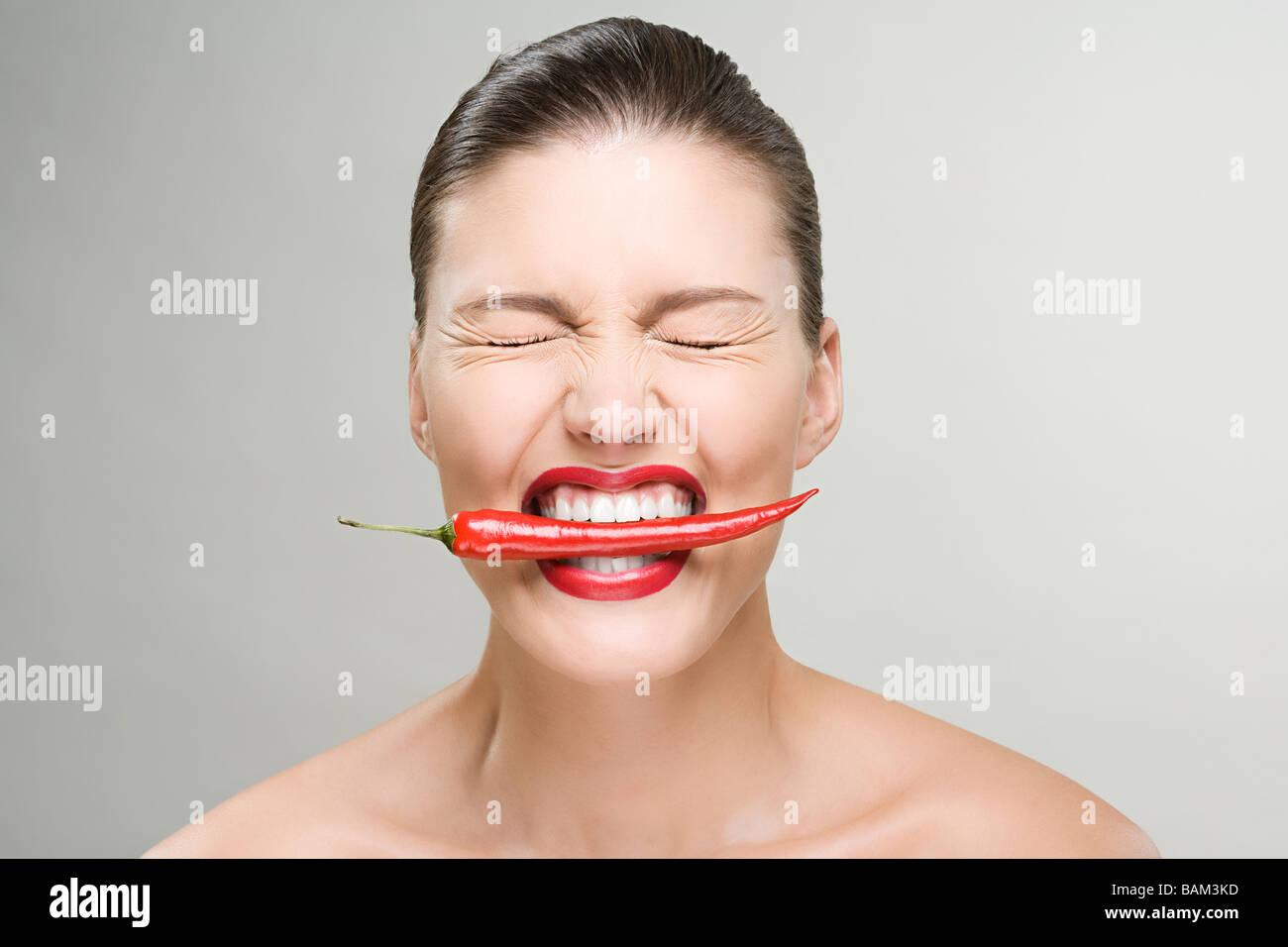 Mujer con un pimiento rojo en su boca Imagen De Stock