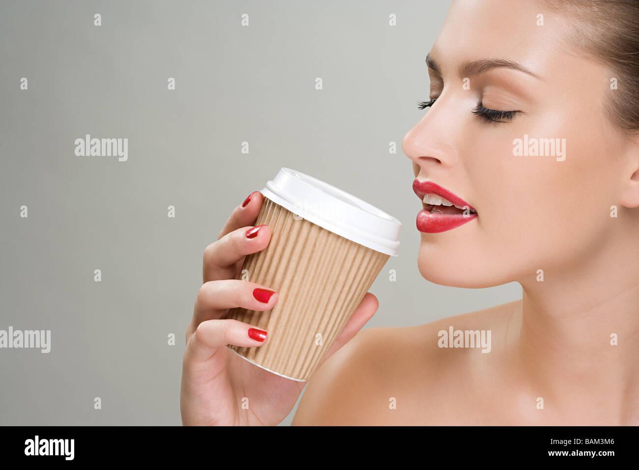 Mujer bebiendo café desde una taza de papel Imagen De Stock