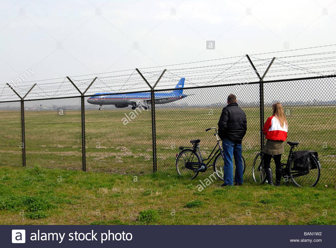 Schiphol Holanda un par ver un bmi British Midland de rodadura del Airbus A321 a través del vallado perimetral Imagen De Stock