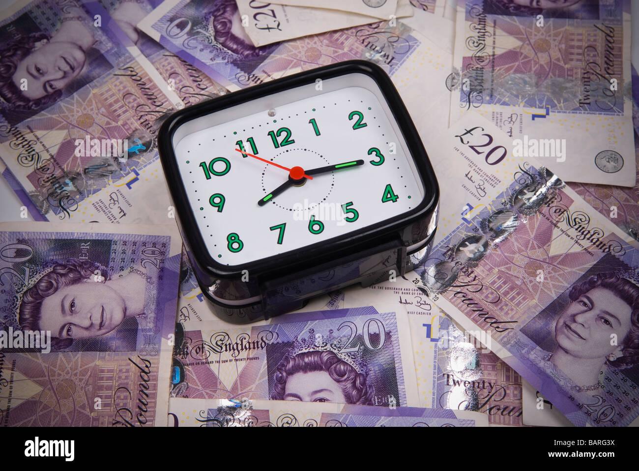 Reloj de alarma sobre un montón de dinero británico Foto de stock