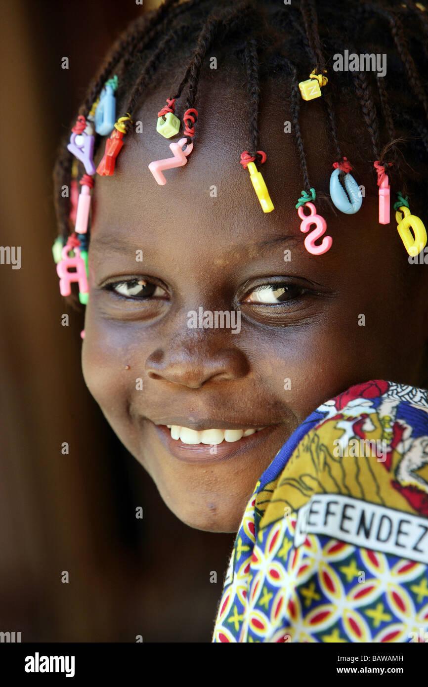 Chica sonriente con letras en sus dreadlocks, Guinea, África occidental Imagen De Stock