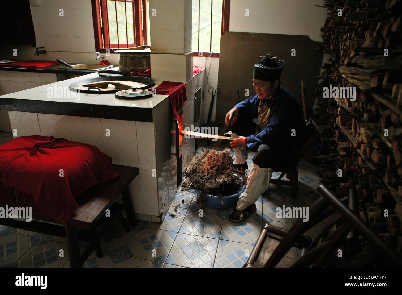 Una monja calentando la estufa en la cocina del Convento Huanting ...