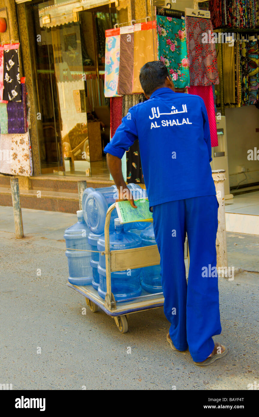 Empleado entregando agua embotellada Dubai Imagen De Stock