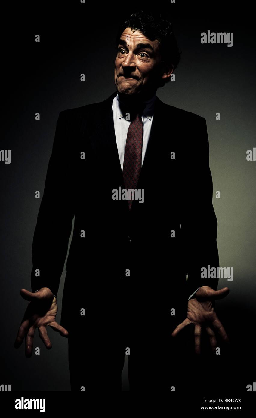 Vista frontal de un hombre maduro en un traje de negocios, mirando a los lados, con las palmas abiertas de par en Imagen De Stock