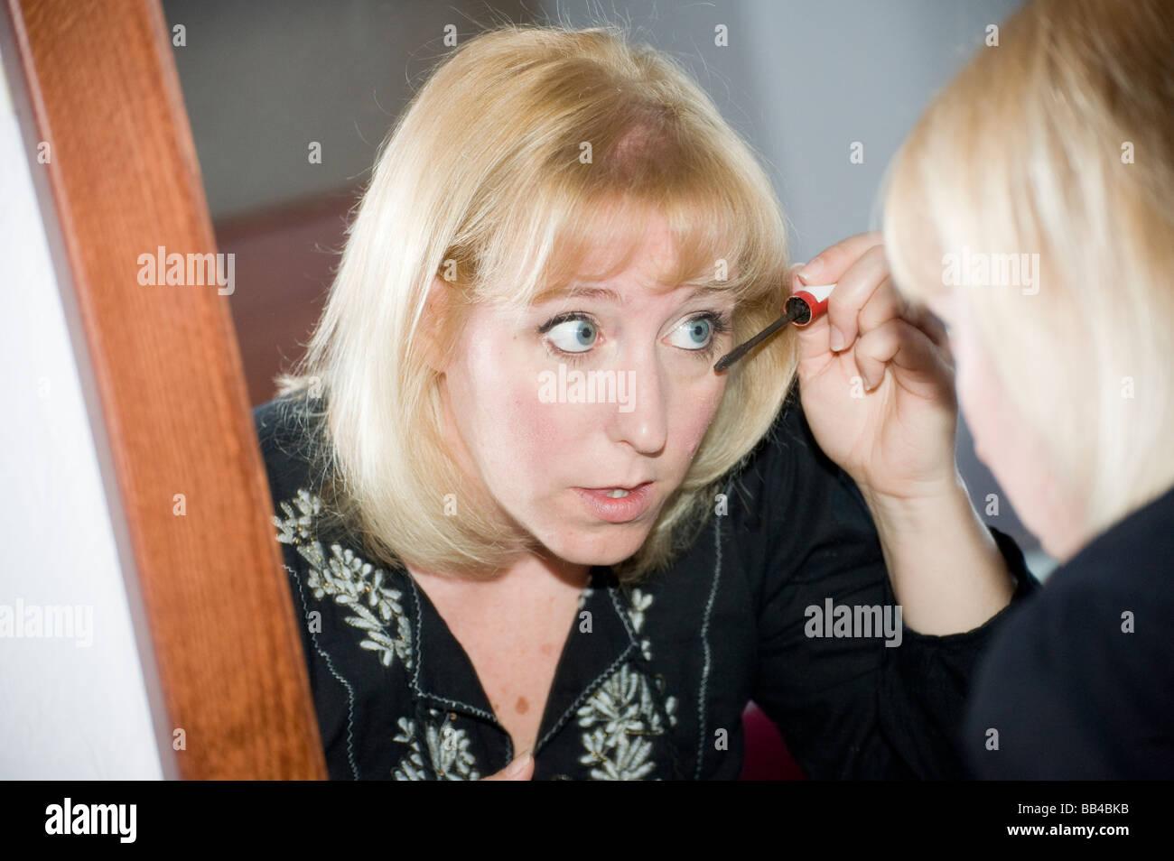 Mujer rubia mirarse a un espejo y aplicar mascara componen Imagen De Stock