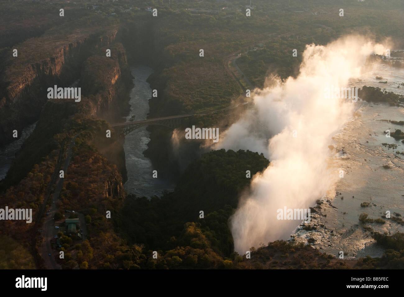 Vista aérea de misty Victoria Falls una de las 7 maravillas naturales del mundo y el puente limítrofe con Zambia Foto de stock