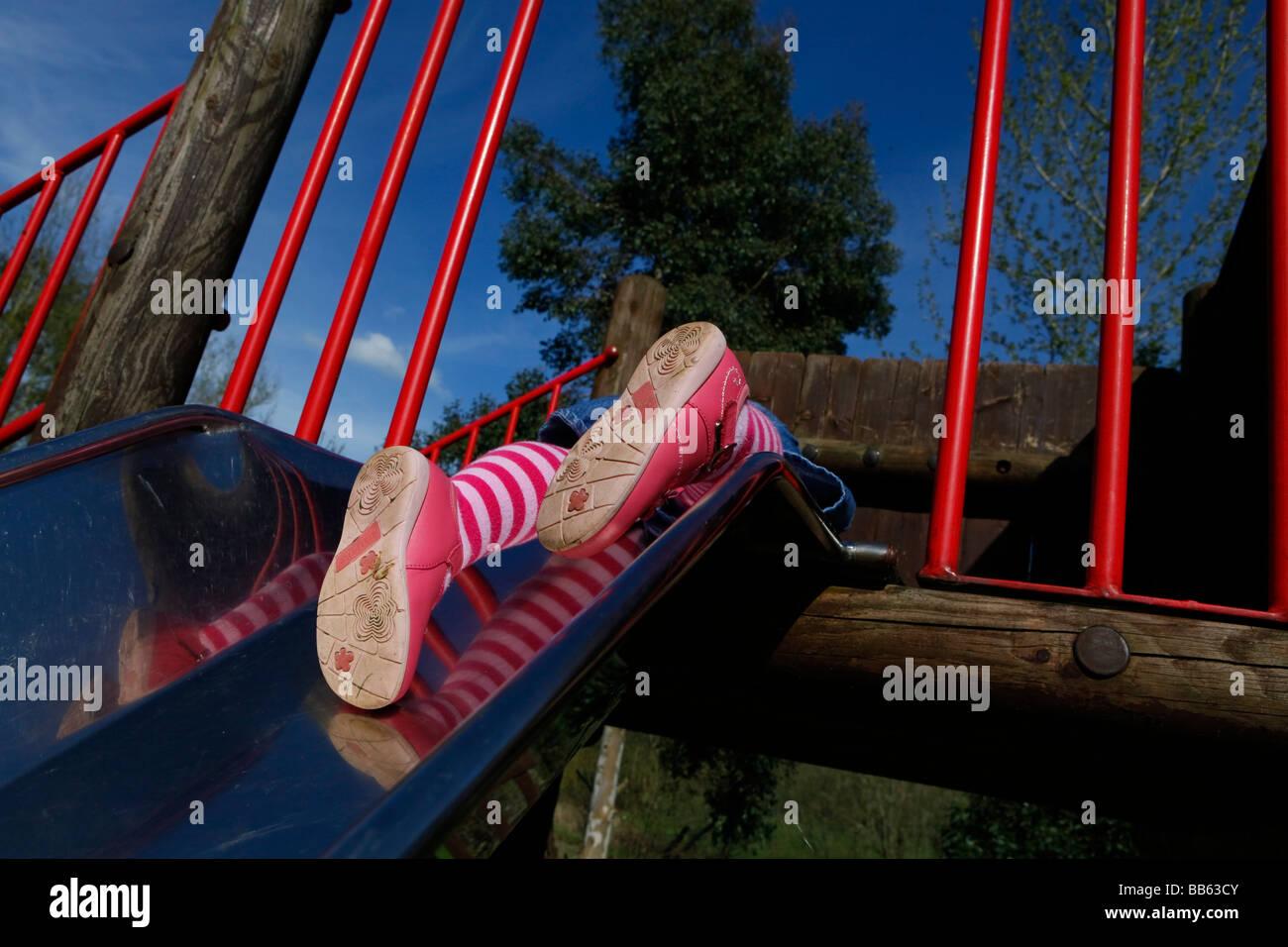 Pies de las niñas que aparecen en la parte superior de la diapositiva en el parque en un día soleado. Imagen De Stock