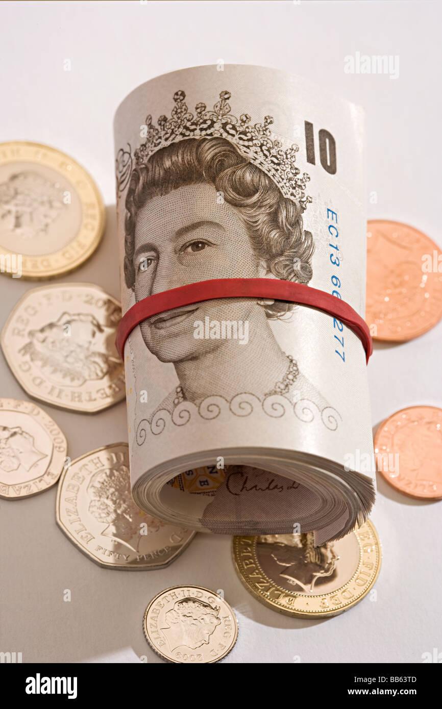 Nuevos y sin rollo de libras esterlinas billetes de diez libras de menta enrolladas acostado en acuñar monedas Imagen De Stock