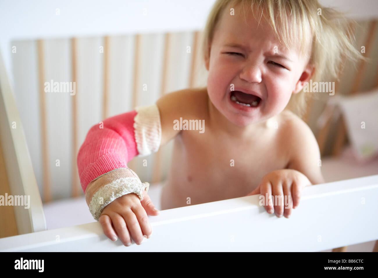 Niño llorando con el brazo en fundición Foto de stock