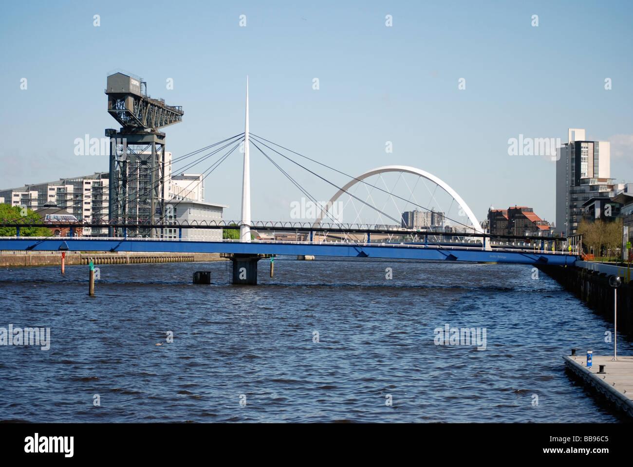 Vista del Río Clyde de Glasgow Squinty Bridge (ARC) y Clyde Finnieston Crane Foto de stock