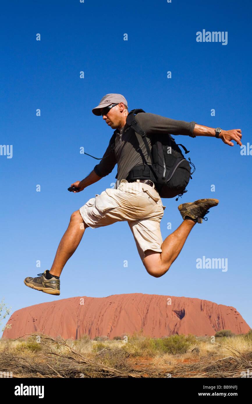 Backpacker saltando sobre Uluru (Ayers Rock). El Parque Nacional de Uluru-Kata Tjuta, el Territorio del Norte, Australia Imagen De Stock