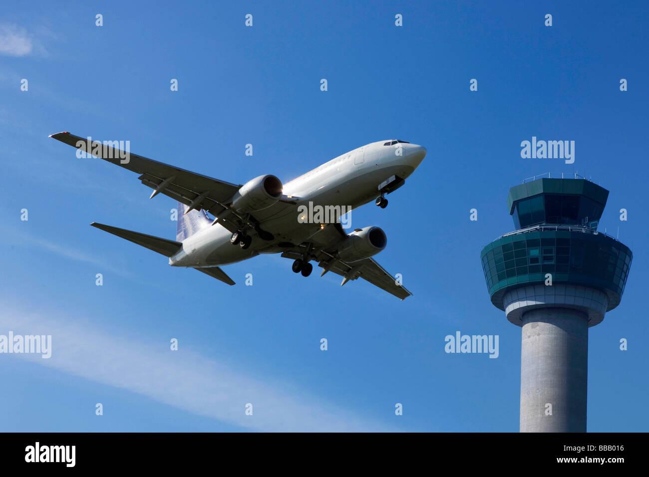 Vuelo de avión pasado la torre de control Foto de stock