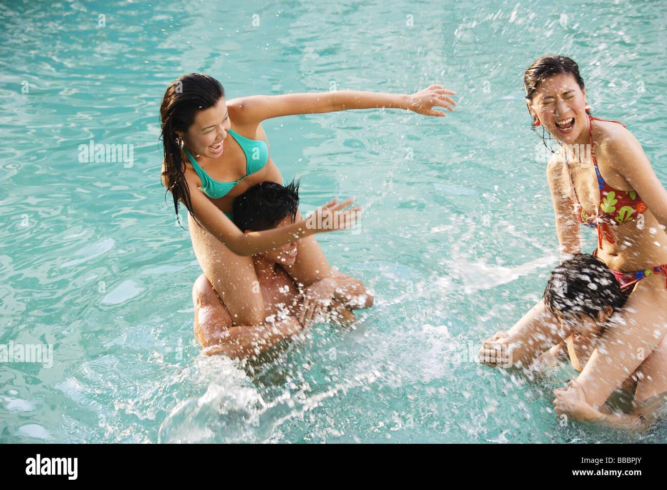Las parejas en la piscina, la mujer sentada sobre los hombros de los hombres Imagen De Stock