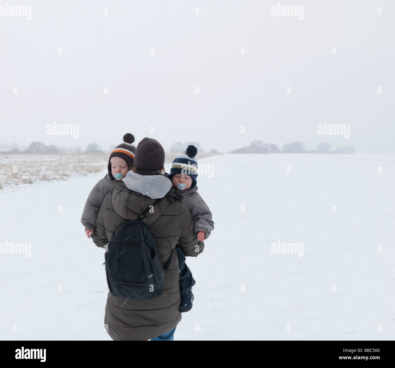 Mujer caminando con dos hijos gemelos en la nieve Imagen De Stock
