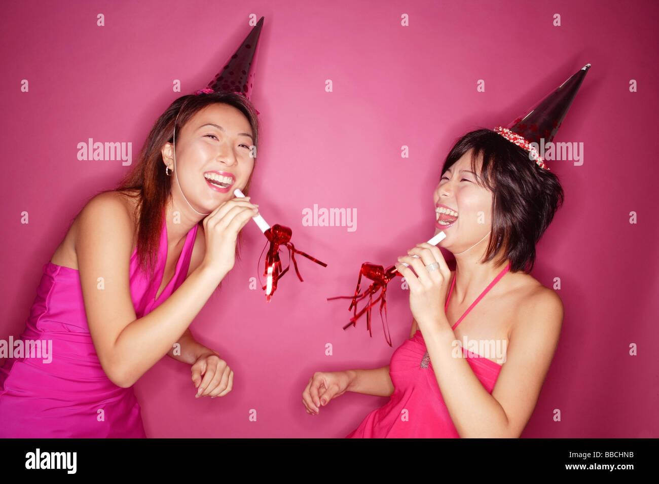 Las mujeres jóvenes con matracas u otros objetos para hacer ruido y gorros  de fiesta 57be4aa7126
