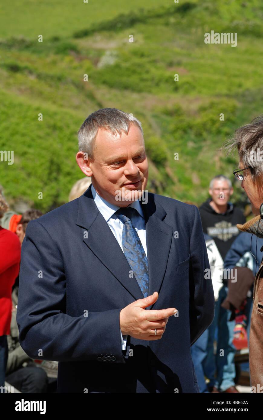 El actor británico Martin Clunes chats durante un descanso en la filmación en Port Isaac en Cornualles, Imagen De Stock