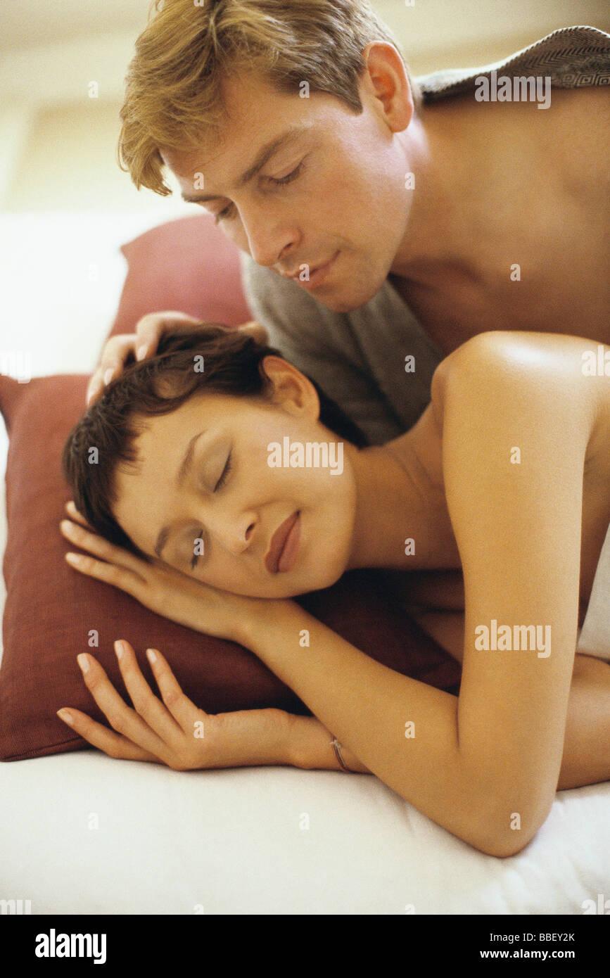 Pareja en la cama, el hombre ve la mujer dormir Imagen De Stock