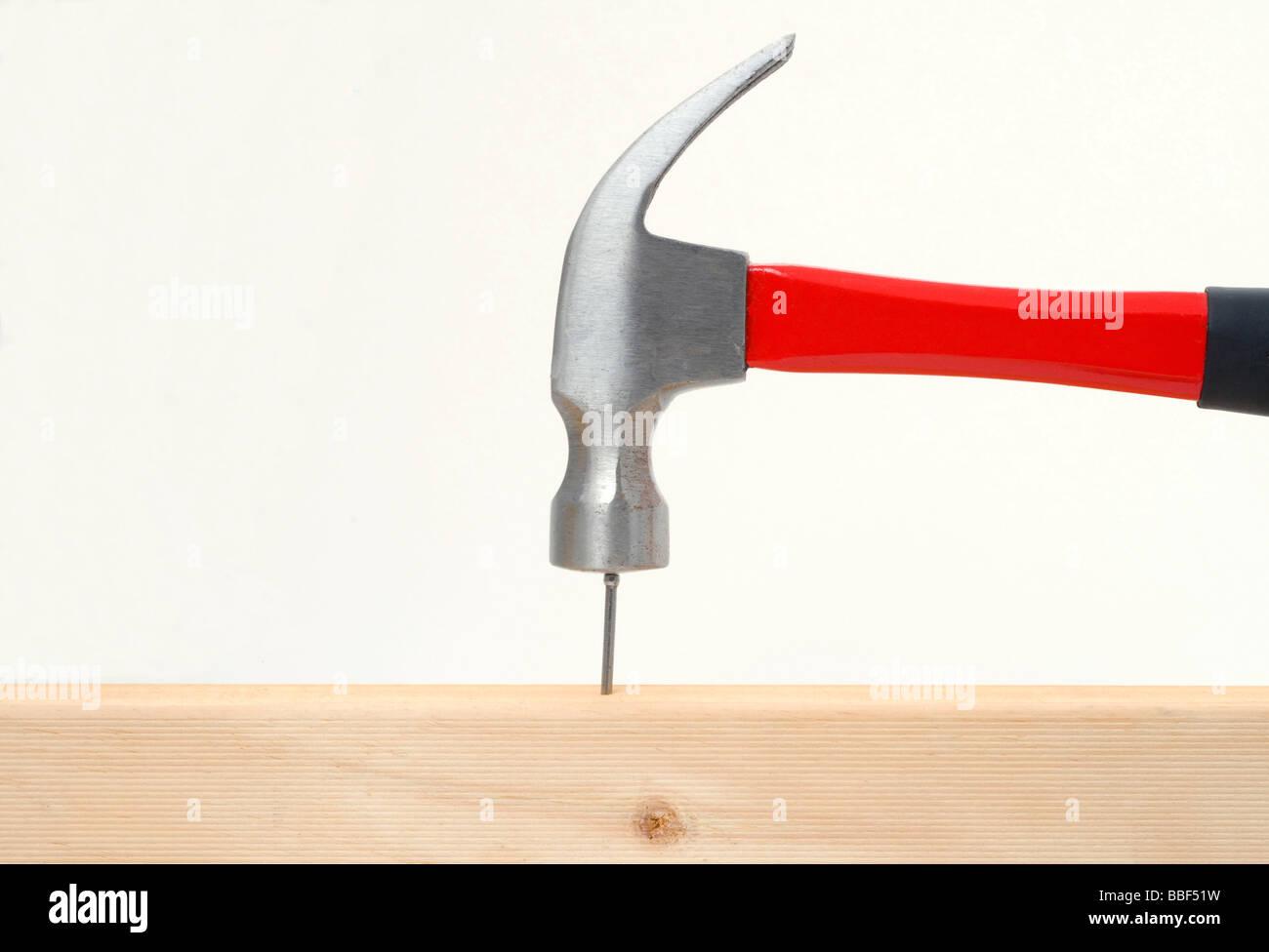 Un martillo golpea un clavo en la cabeza en woood Imagen De Stock