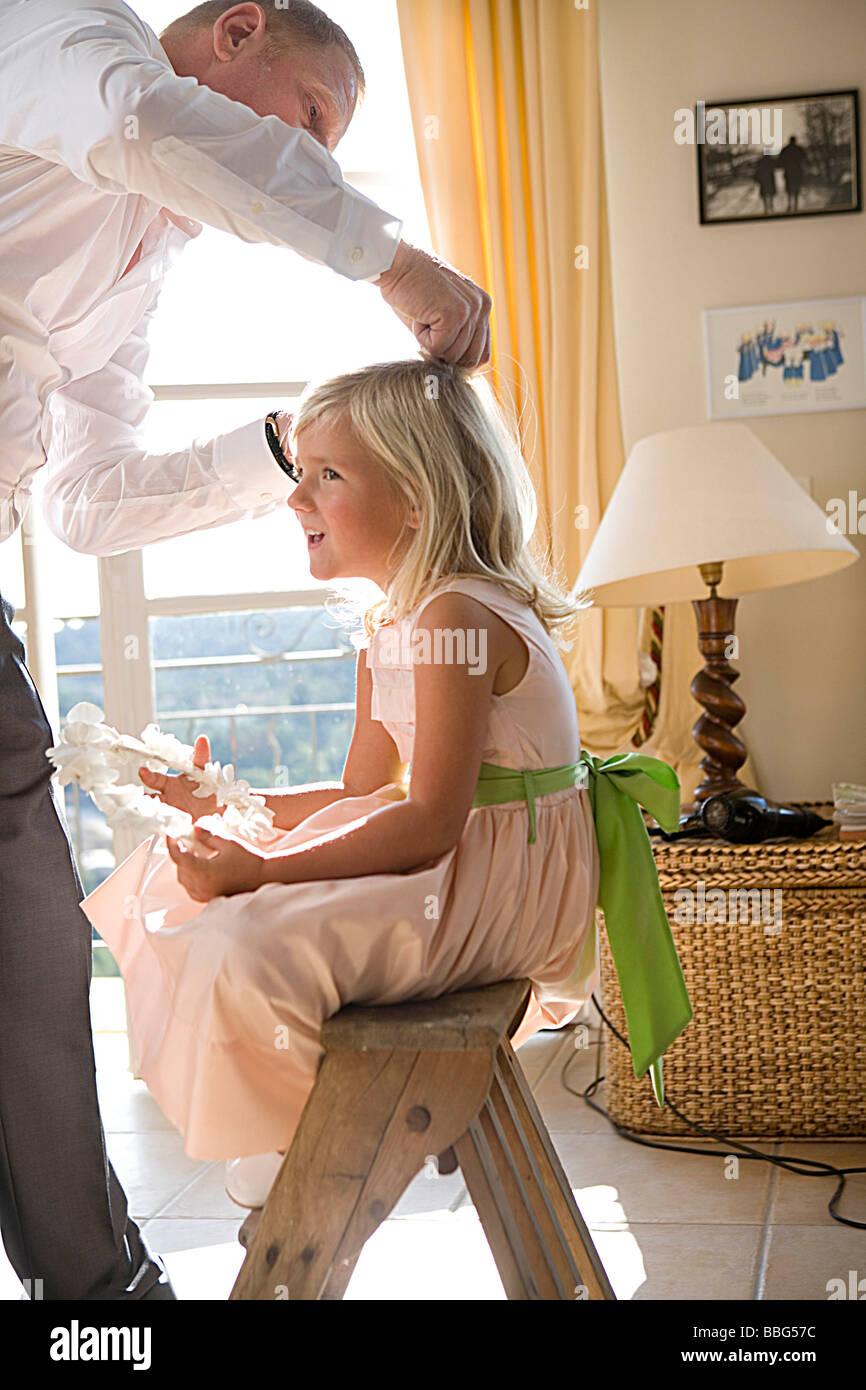 El padre prepara el cabello de la chica Foto de stock