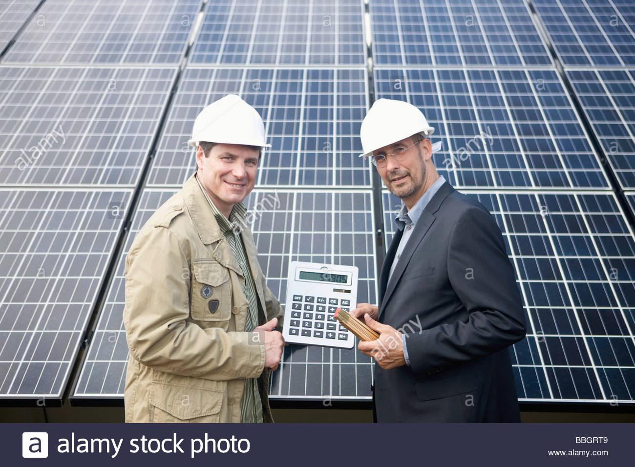 Empresarios maduros sosteniendo una calculadora solar delantero panelado, Munich, Baviera, Alemania Imagen De Stock