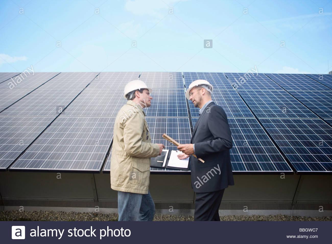 Empresarios maduros hablando delante de paneles solares, Munich, Alemania Imagen De Stock