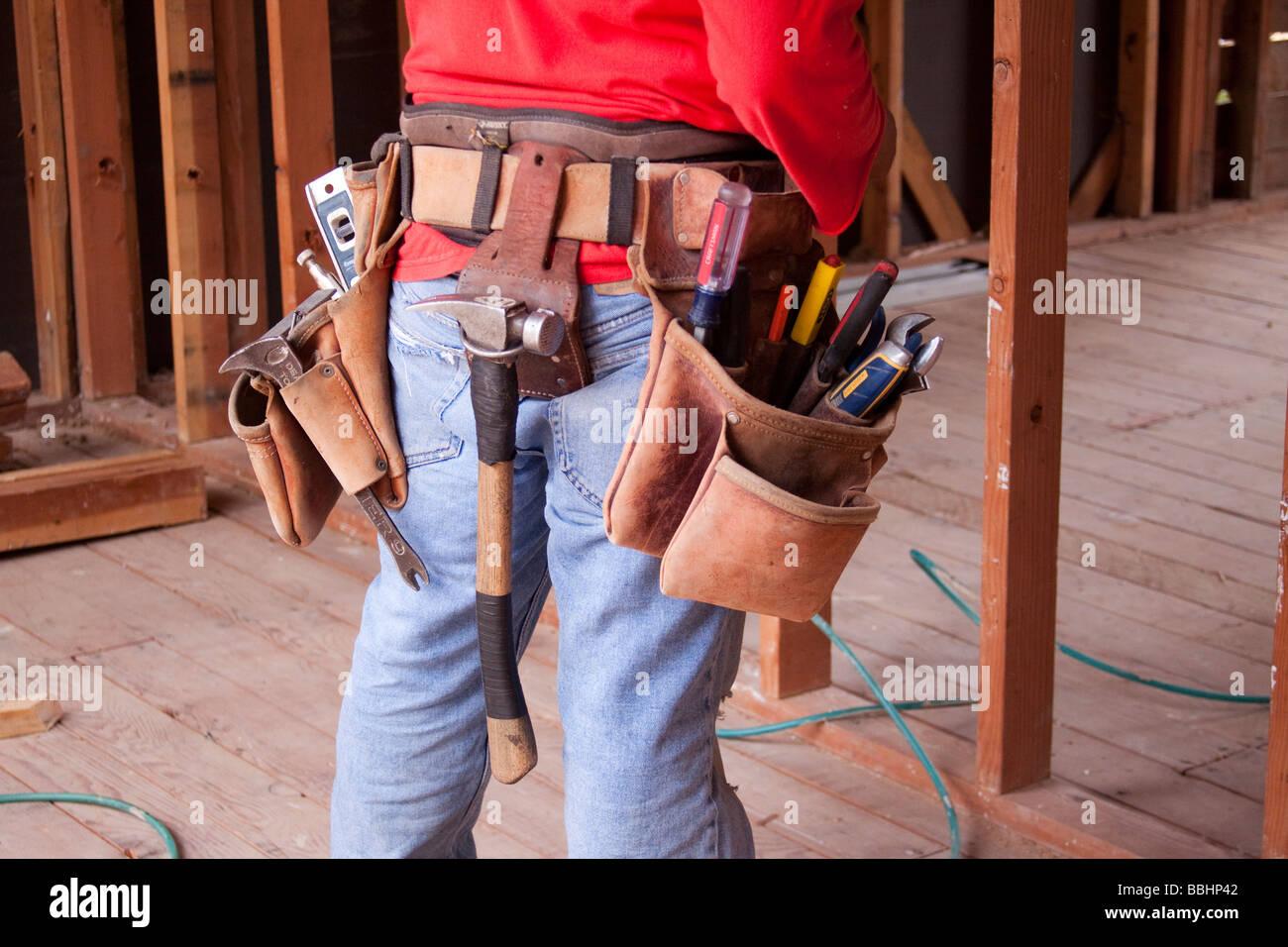 Carpenter vistiendo un cinturón para herramientas de cuero con un surtido  de herramientas en un trabajo de construcción f7f4eece28a8