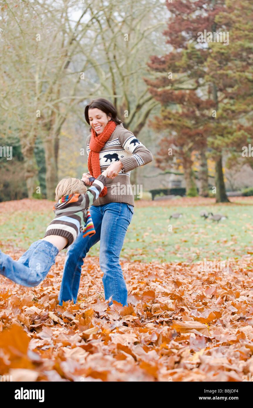 Mamá columpios hijo alrededor en hojas de otoño, Vancouver, British Columbia Foto de stock