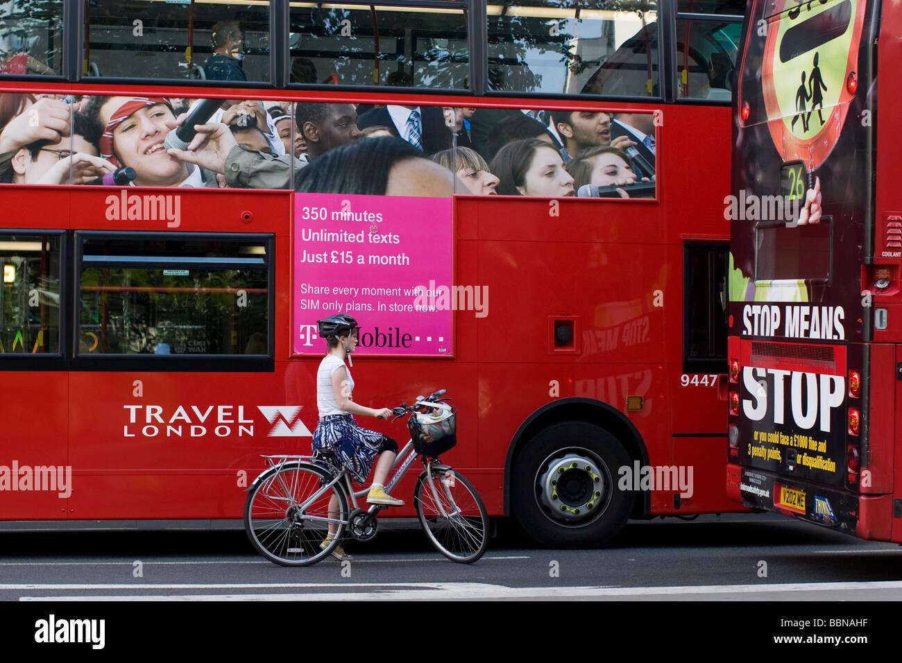 Hembra con casco de ciclista, entre autobuses de Londres Imagen De Stock