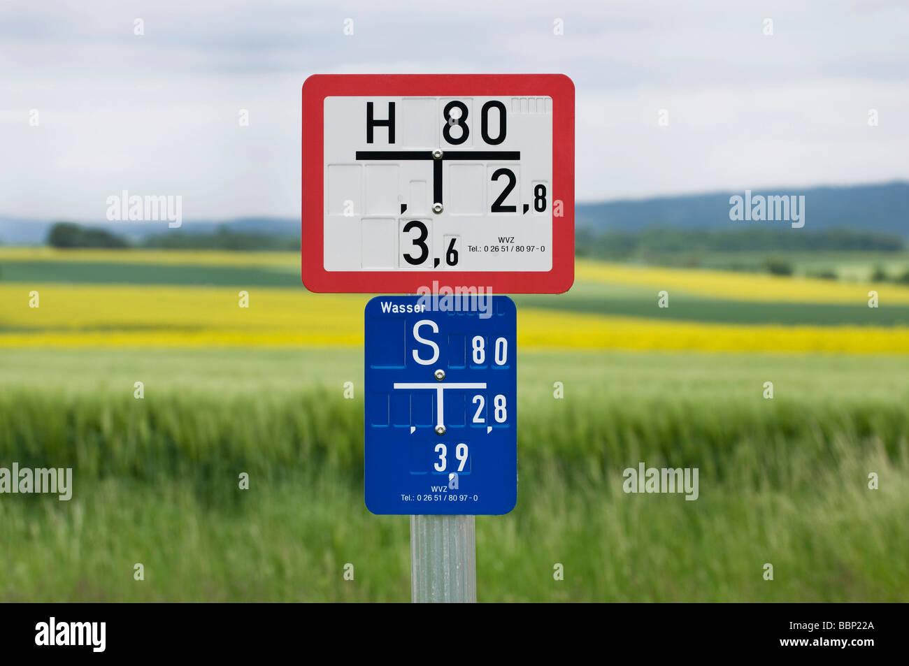 Signo de hidrantes de agua con placa deslizante, campos en la espalda Imagen De Stock