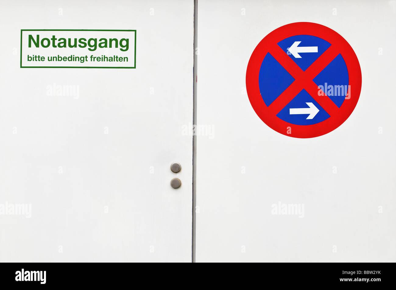 Puerta blanca con señal de salida de emergencia, no bloquear, parar la restricción a la izquierda y derecha Imagen De Stock