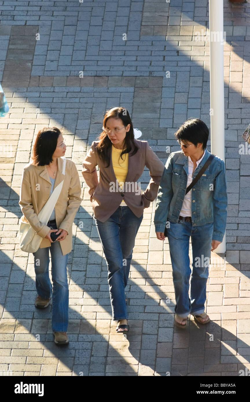 Tres amigos asiáticos caminando por el distrito turístico de Circular Quay. Sydney, Australia. Foto de stock
