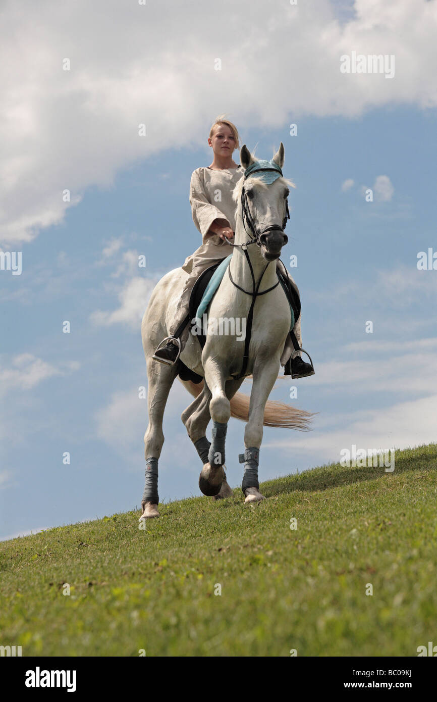 Chica cabalgatas en la colina Foto de stock