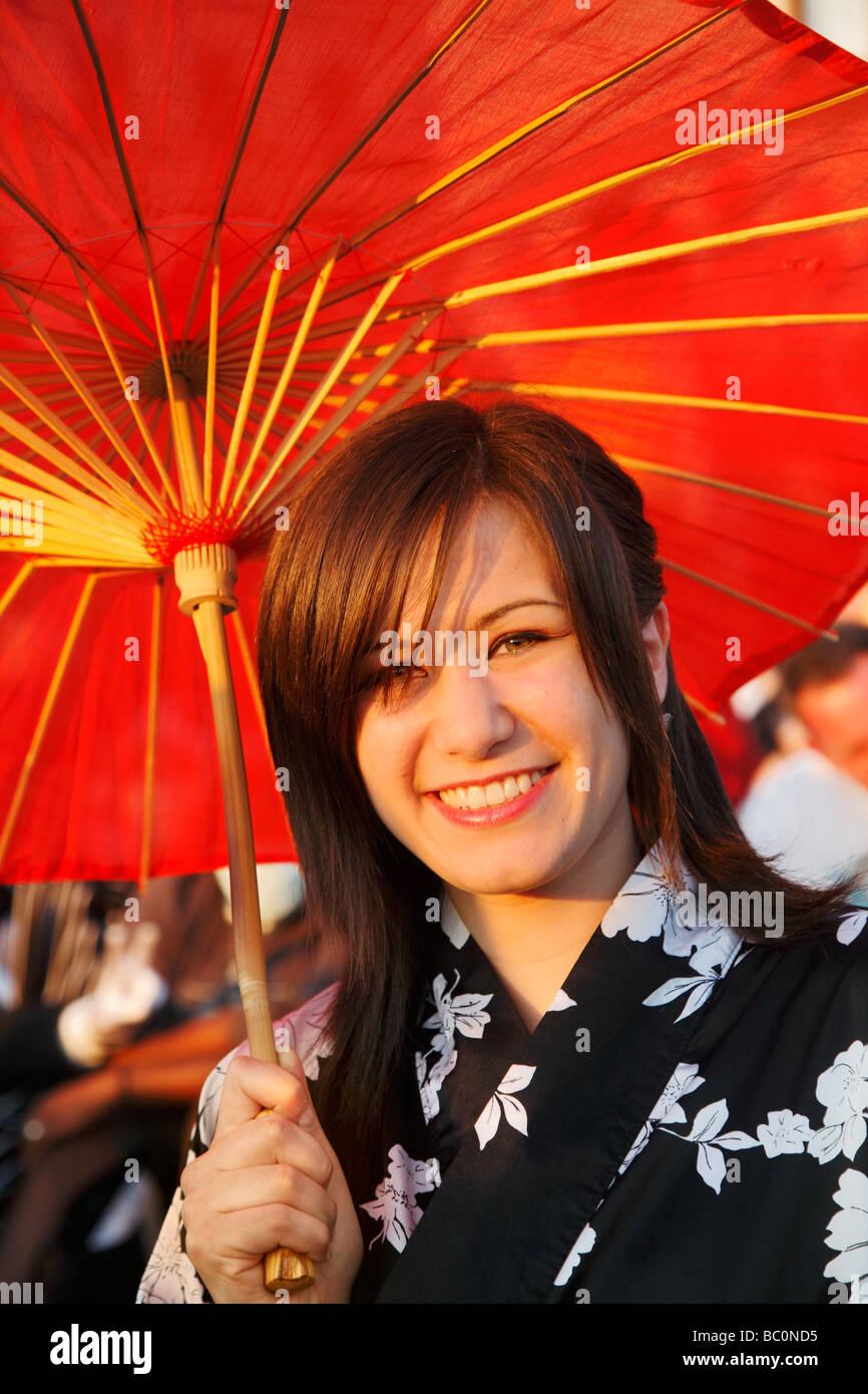 Joven vistiendo un kimono blanco y negro rojo con una sombrilla de papel japonés en el día Japonés Imagen De Stock