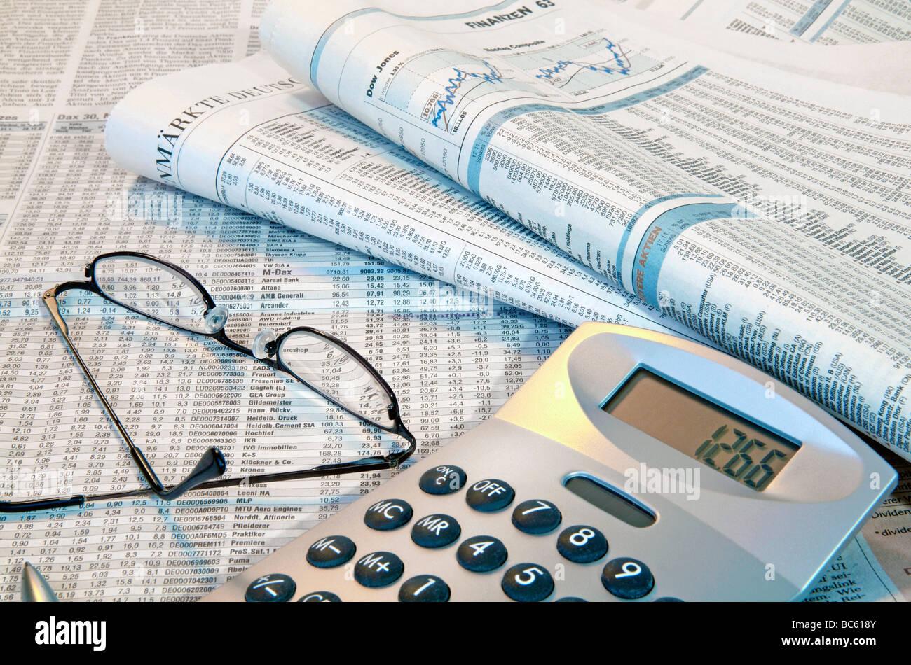 Cierre de periódicos financieros con gafas y calculadora Foto de stock
