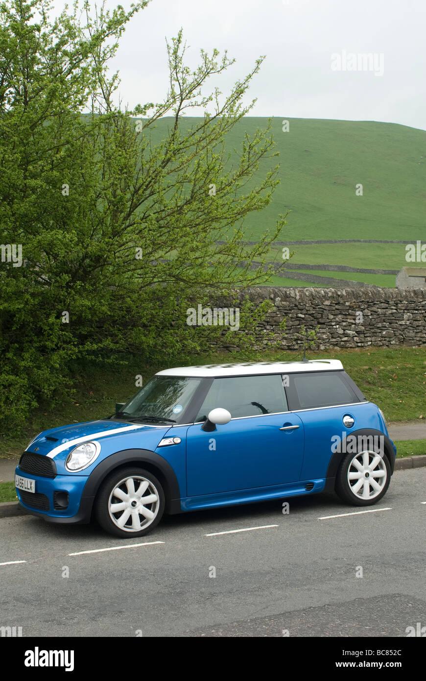 Blue Mini Cooper S coche aparcado al lado de la carretera en un pueblo de la campiña inglesa Imagen De Stock