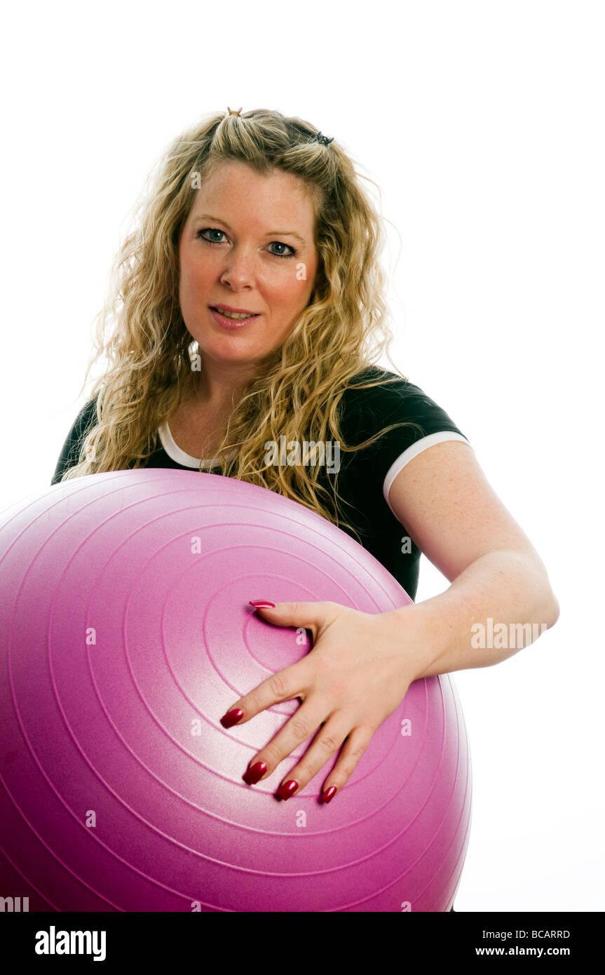 Plus size bonita mujer de mediana edad hacer ejercicio y trabajar con pelota de entrenamiento básico Foto de stock
