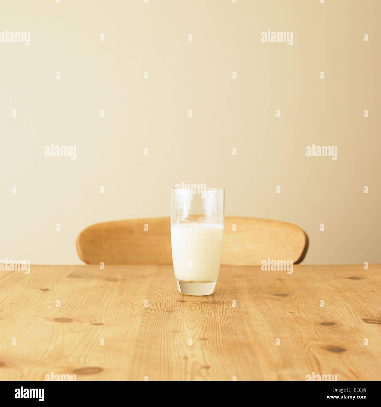 Vaso de leche en la mesa de la cocina de estilo rústico. Imagen De Stock