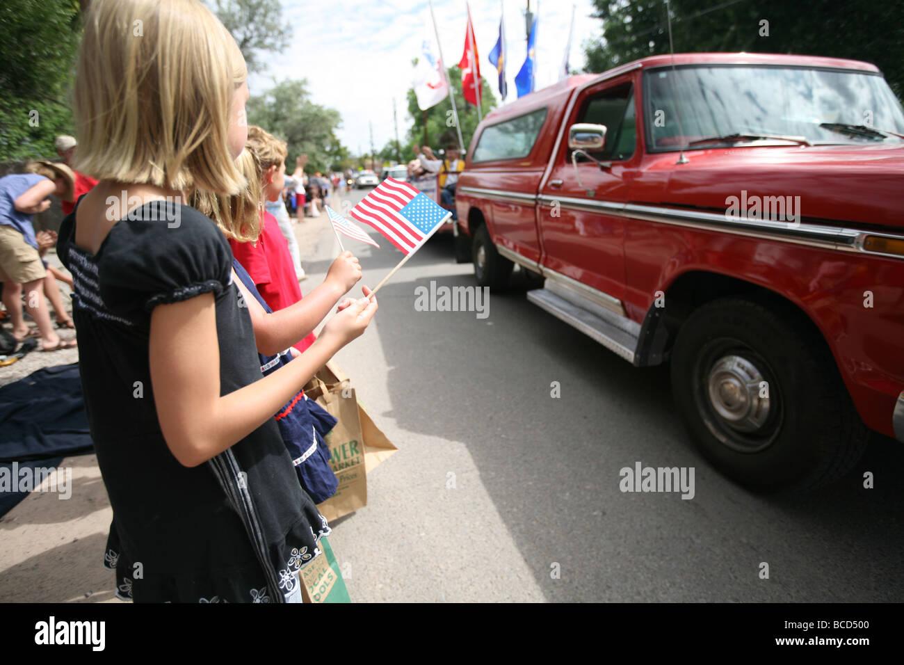Niños portando la bandera estadounidense en el desfile del 4 de julio Imagen De Stock