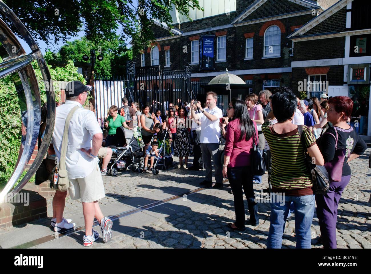 Londres, Reino Unido - Los Turistas posar para fotos en el marcador del primer meridiano del mundo en el Observatorio Imagen De Stock