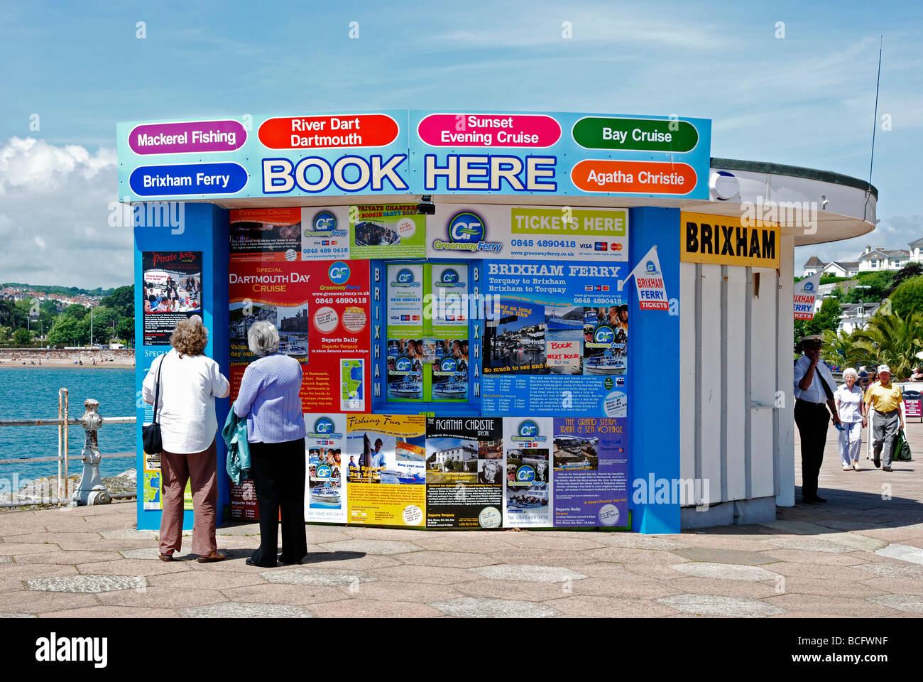 Dos señoras mayores mirando para reservar una excursión en Torquay, en Devon, Reino Unido Imagen De Stock