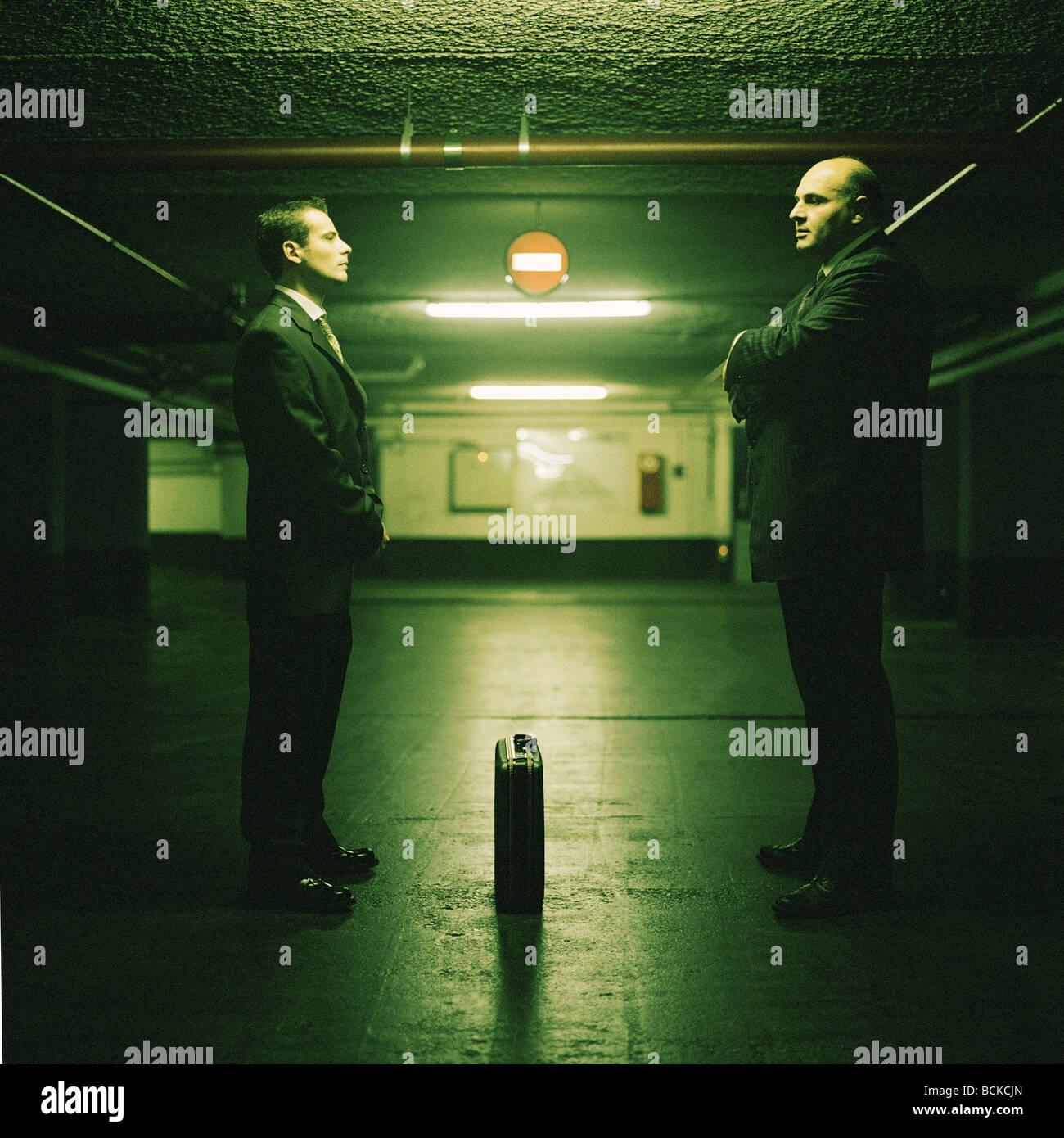 Garaje, dos hombres cara a cara con el maletín entre ellos Imagen De Stock