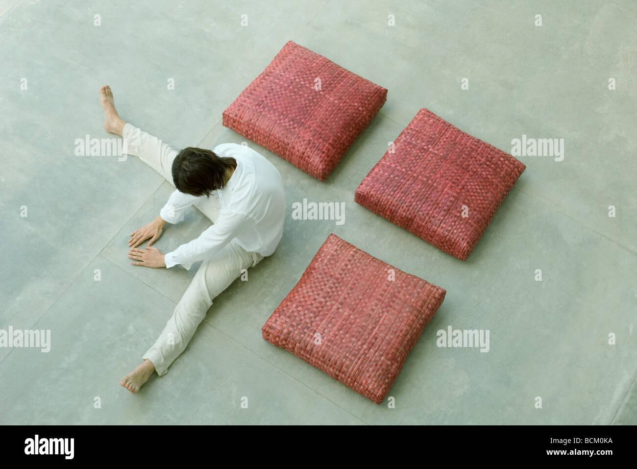 Tres almohadones cuadrados y man dispuestos en forma cuadrada, hombre inclinarse hacia delante con piernas separadas, Imagen De Stock