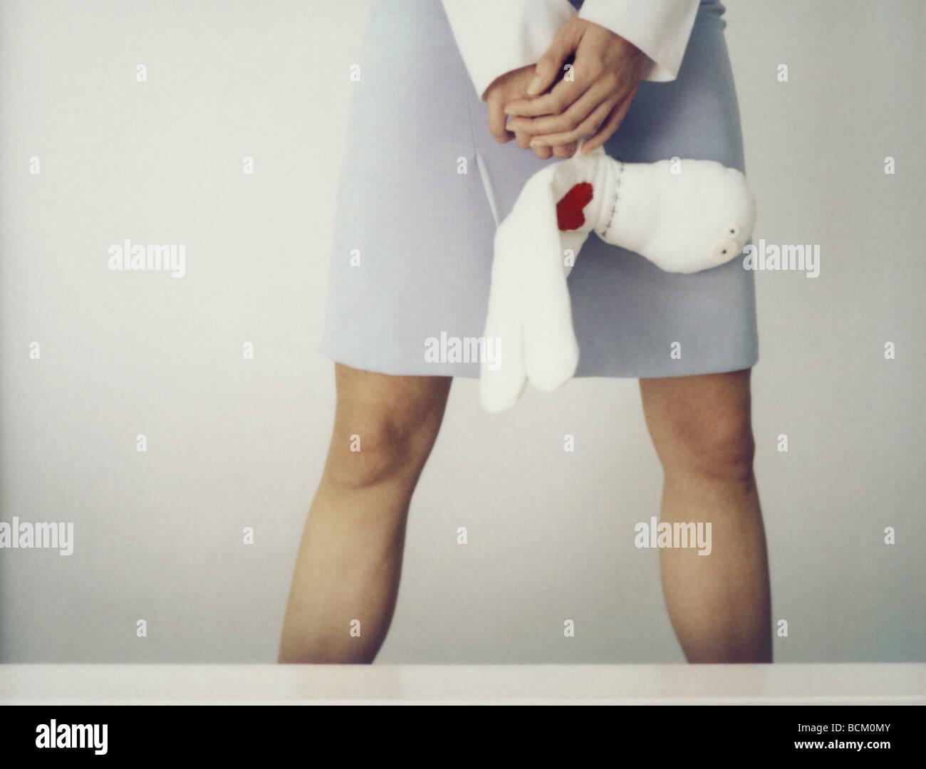 Mujer de pie con las piernas, manteniendo rag doll en manos entrelazadas, vista recortada piernas Imagen De Stock