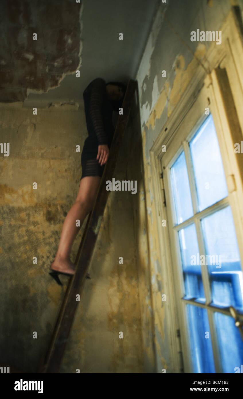 Mujer de pie sobre la escalera en la esquina de la habitación, la cabeza inclinada hacia abajo bajo el techo, longitud Foto de stock