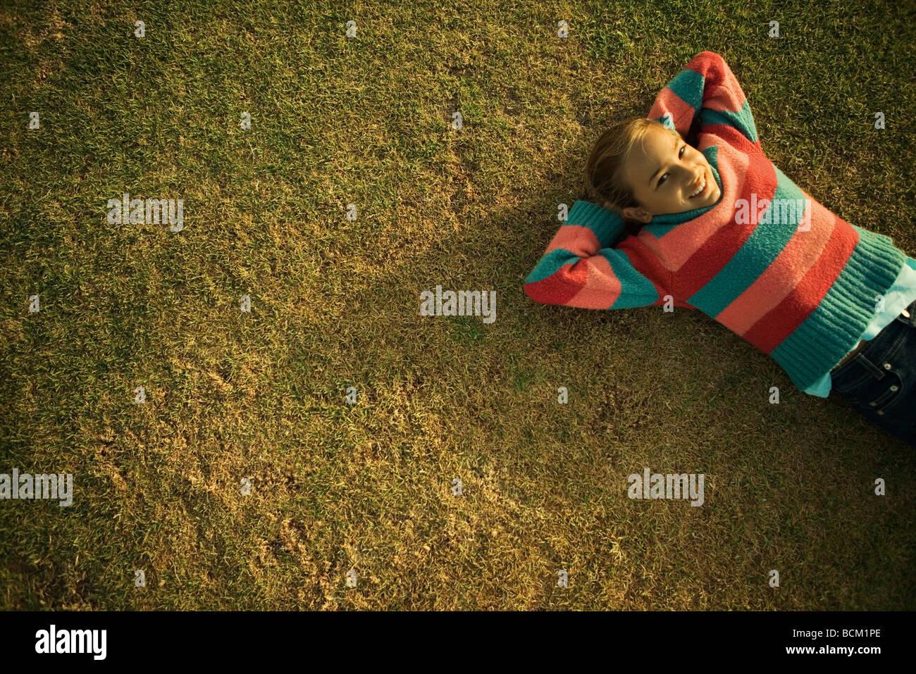 Chica tumbado en la hierba con las manos detrás de la cabeza, un alto ángulo de visualización Imagen De Stock