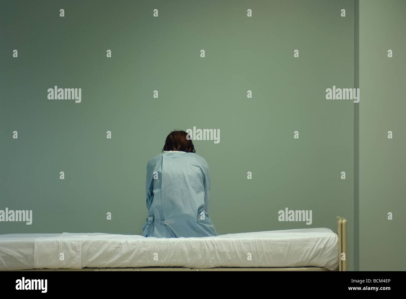Paciente mujer sentada en la cama de un hospital, con la cabeza hacia abajo, vista trasera Imagen De Stock