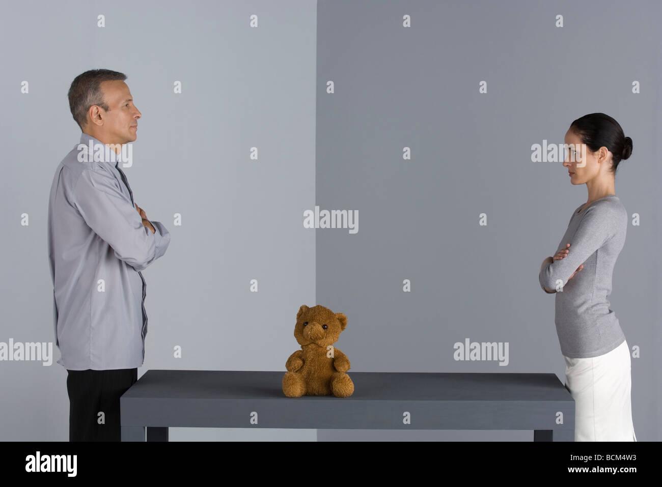Par de pie frente a frente en la mesa, con los brazos plegados, entre ellos oso de peluche Foto de stock