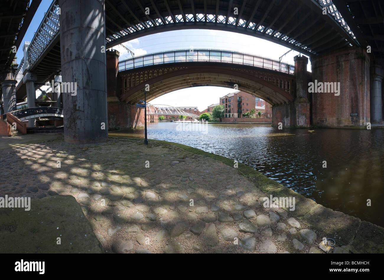 Mirando a través de victoriano viaductos ferroviarios hacia el Puente de los comerciantes en el Castlefield basin Manchester Foto de stock