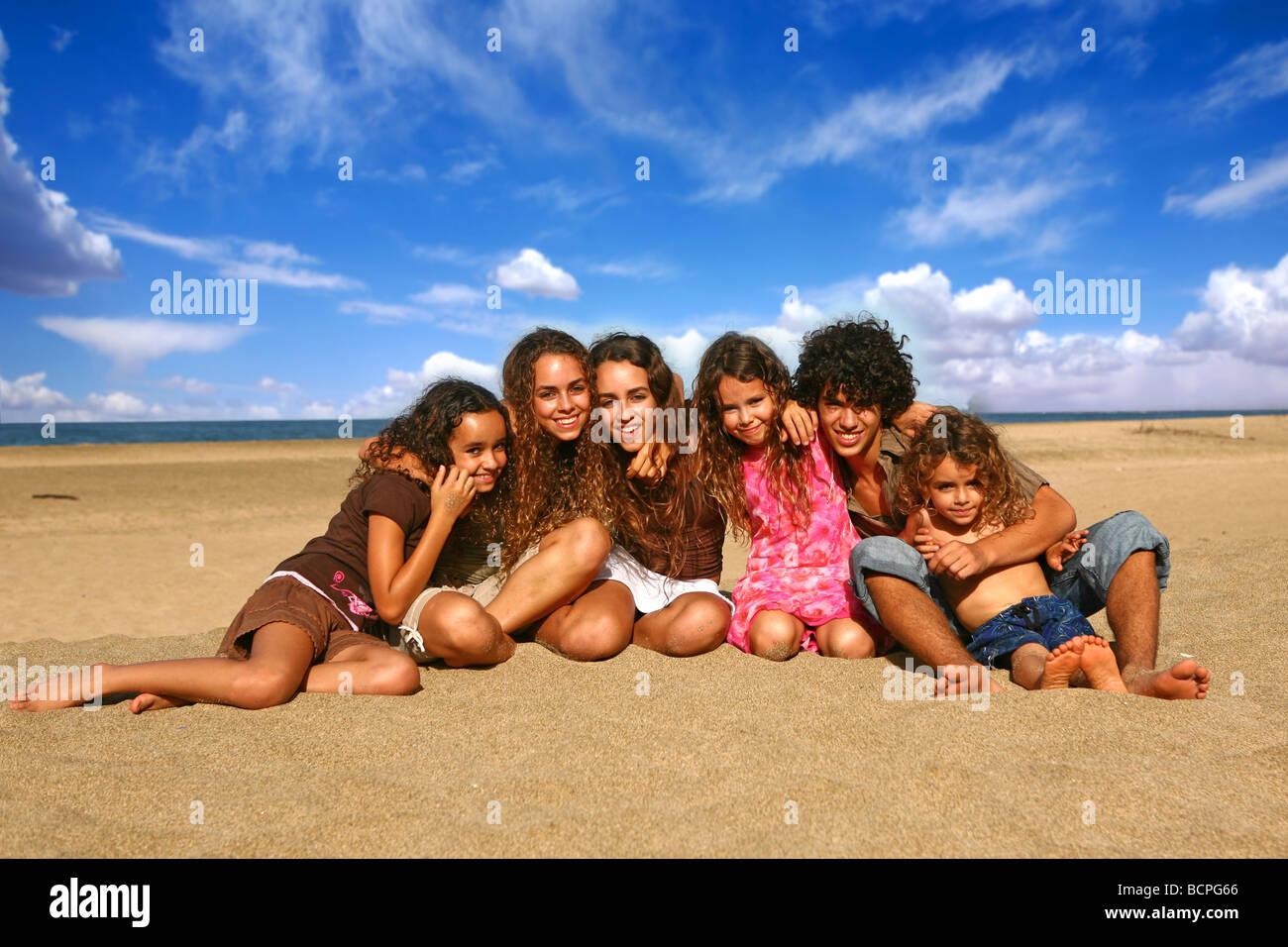 Familia de 6 niños felices, sonriendo al aire libre en la playa. Imagen De Stock